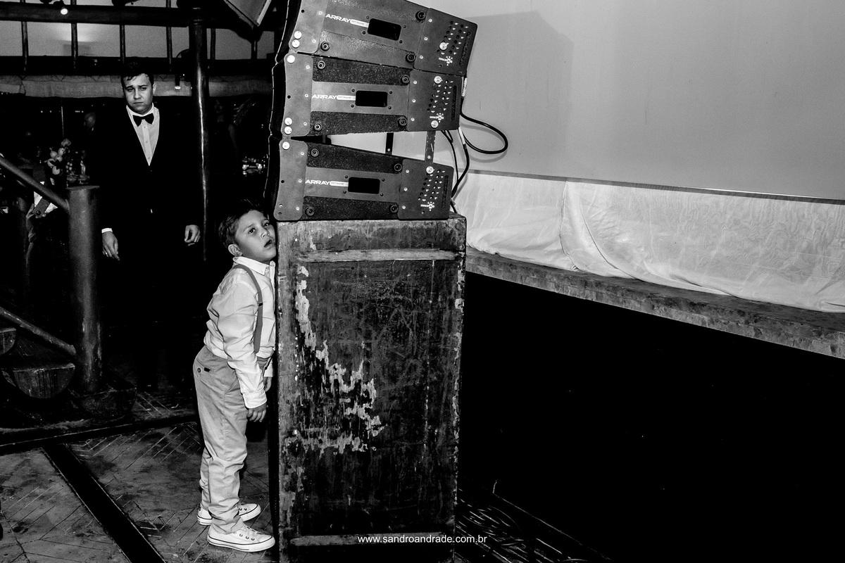 retrato de um menininho durante a festa que encostou a cabeça na caixa de som com carinha de sono sentindo a vibração da caixa, rsrsrs