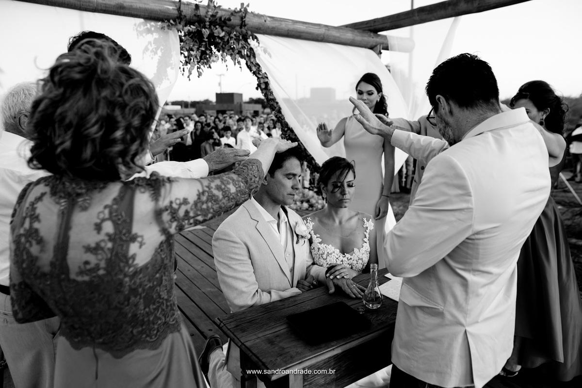 Momento da benção sobre a vida do mais novo casal, rodeados pelo pastor, pais e filhos do noivo.