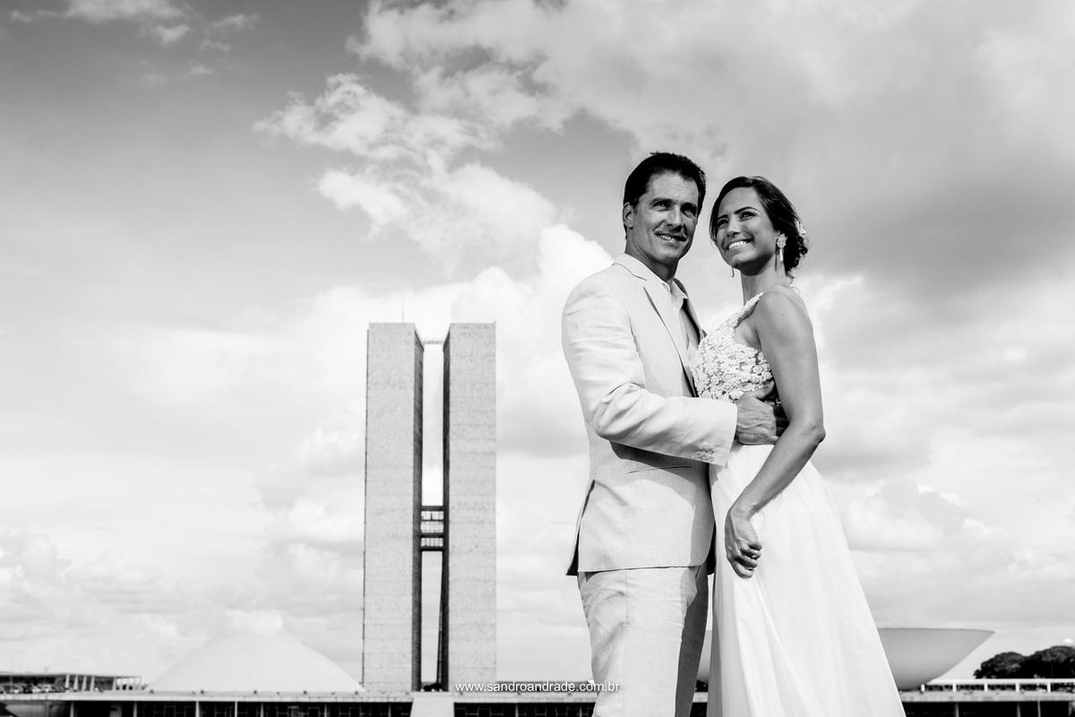 O casal posa para a foto com o congresso nacional de fundo, local onde trabalham, se conheceram e iniciaram sua historia de amor.