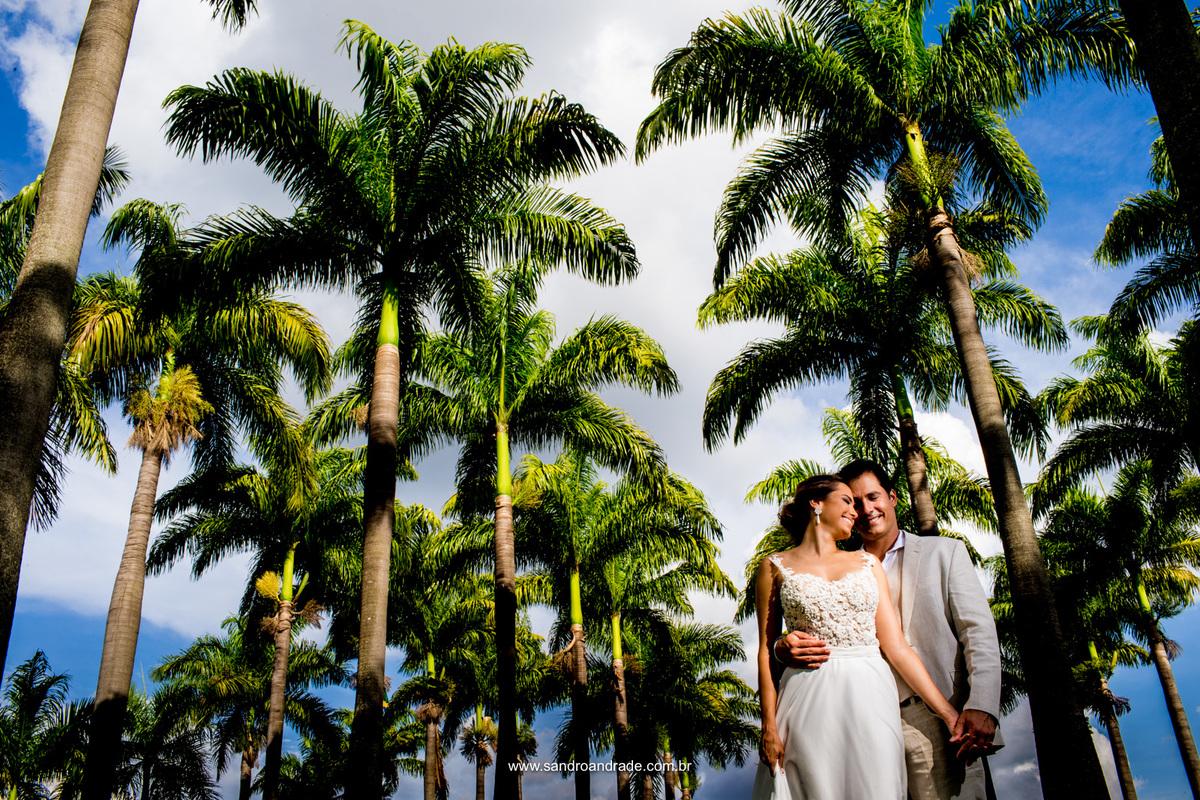 Linda fotografia bem contrastada, eles de branco, o verde das palmeiras e esse lindo céu azul carregado de nuvens
