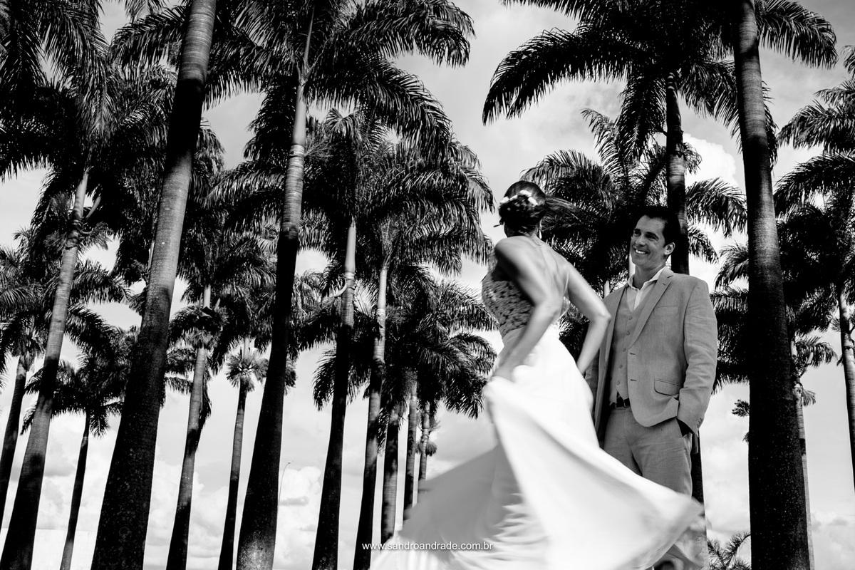 Encantado ele olha para sua amada, todo feliz e sorridente, enquanto ela parece flutuar em seu vestido de noiva