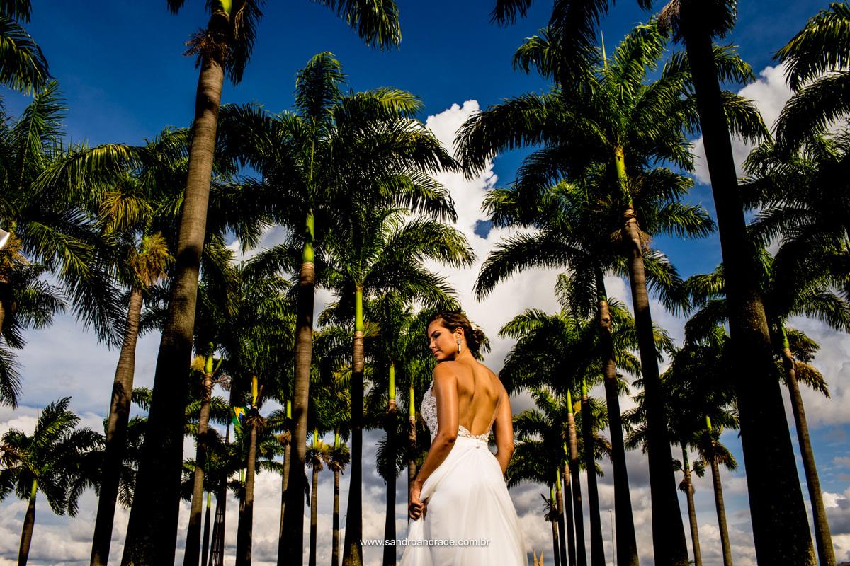 Retrato da noiva, ela de costas para mostrar os detalhes de seu lindo vestido em contraste com céu azul e as palmeiras