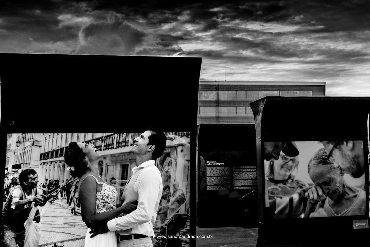 Gangalhando em meio aos registros de tantos artistas Sandro Andrade compõe a fotografia do casal com a fotografia da exposição.