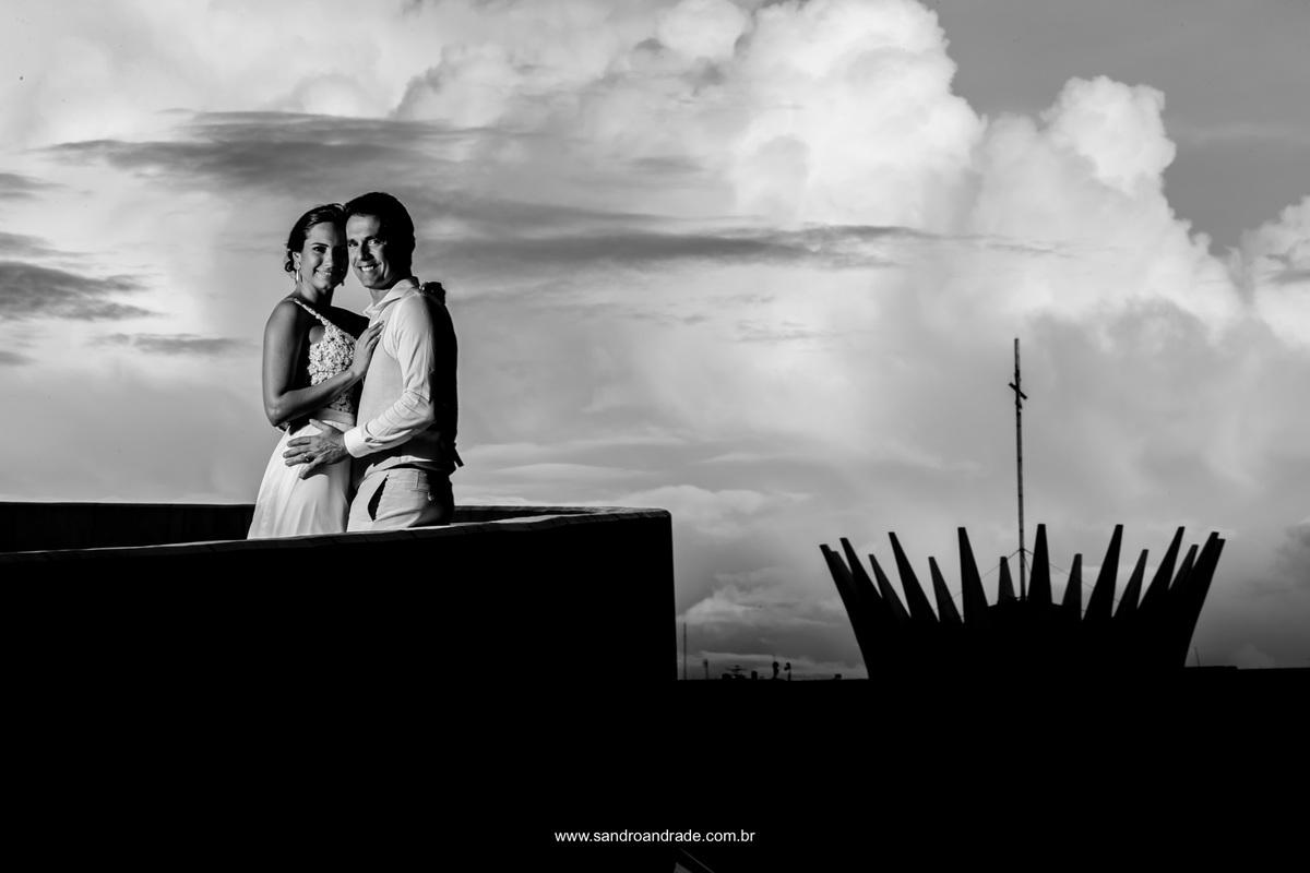 Retrato do casal feito do alto do museu nacional, pegando a coroa da catedral de Brasília.