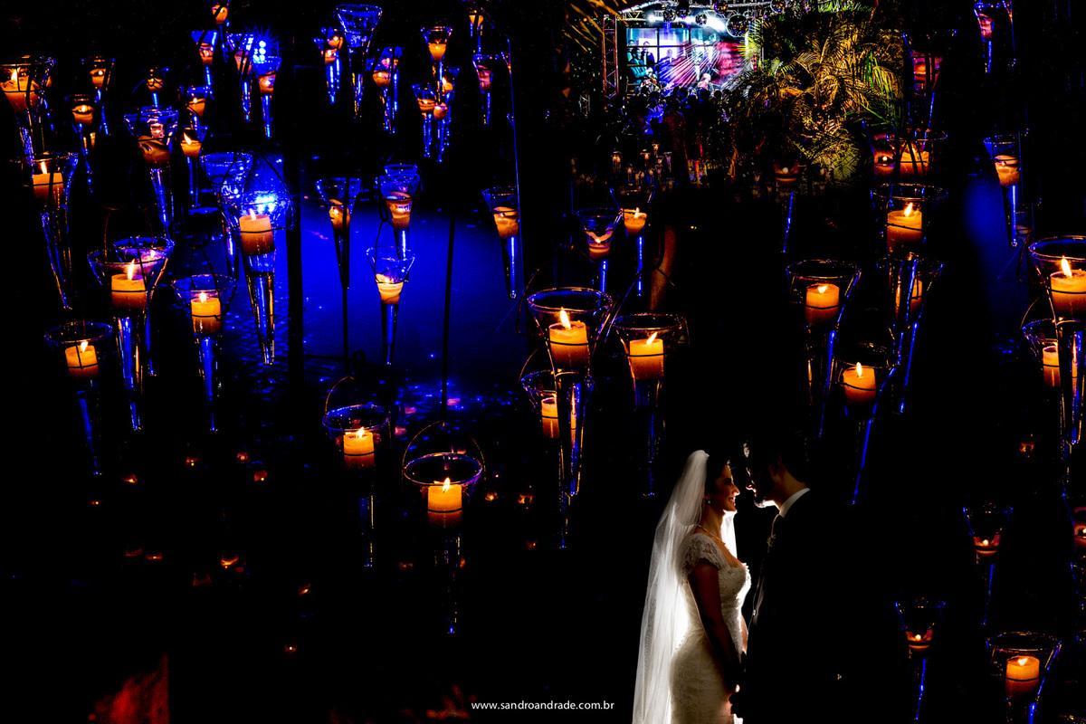 Uma belissima imagem com dupla exposição, dos noivos, com a festa e os lustres.