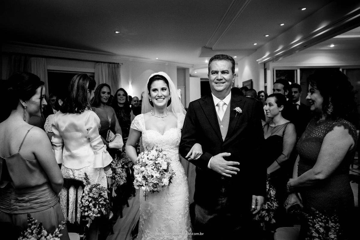 Entrada da noiva com o pai, ela com um sorriso irradiante