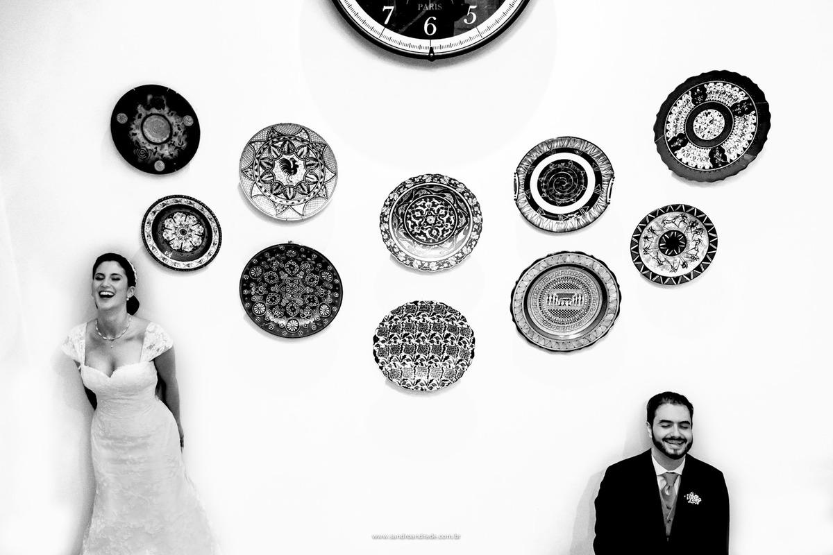 Os noivos sorriem em uma bela fotografia composta pelos pratos que a mãe do noivo comprou em cada viagem que fez.