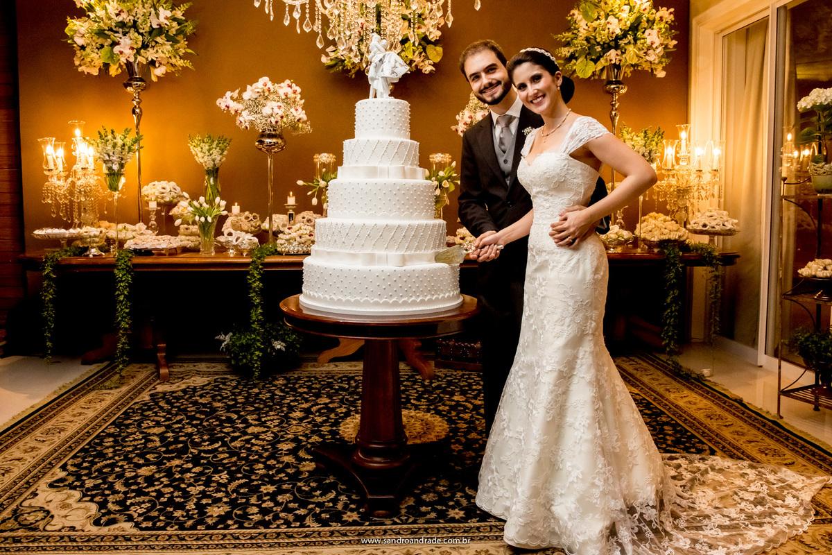 O corte do bolo, noivos lindos e felizes.