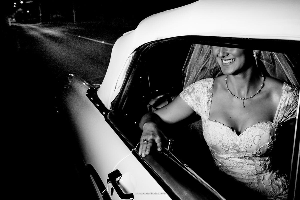 Dentro de um lindo carro antigo, ela sorri a espera do momento de sua entrada
