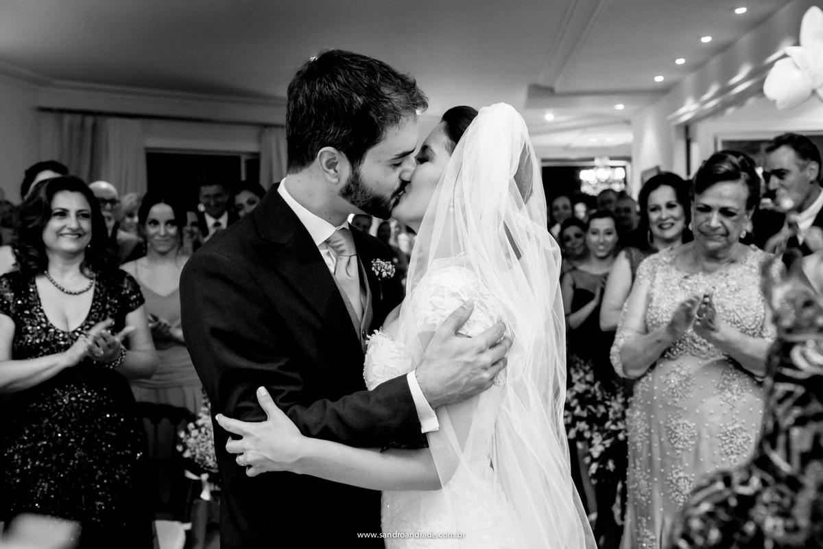 o beijo dos noivos sob aplausos dos convidados