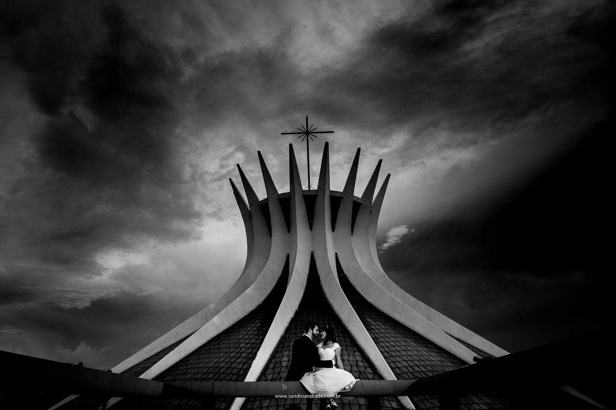 Catedral de Brasilia, uma linda fotografia preto e branco bem contrastado com um céu dramatico carregado em nuvens e o casal a frente.