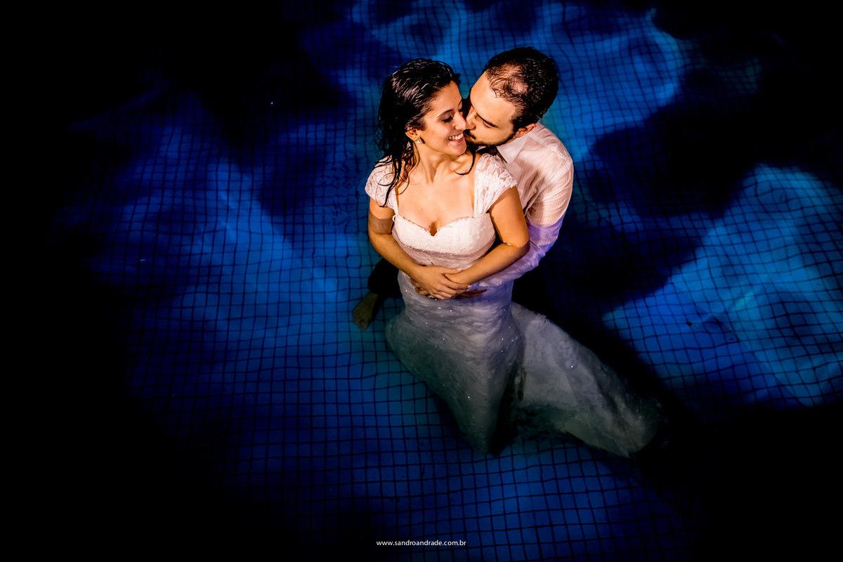 Belissimo azul em contraste com a roupa dos noivos no fundo da piscina