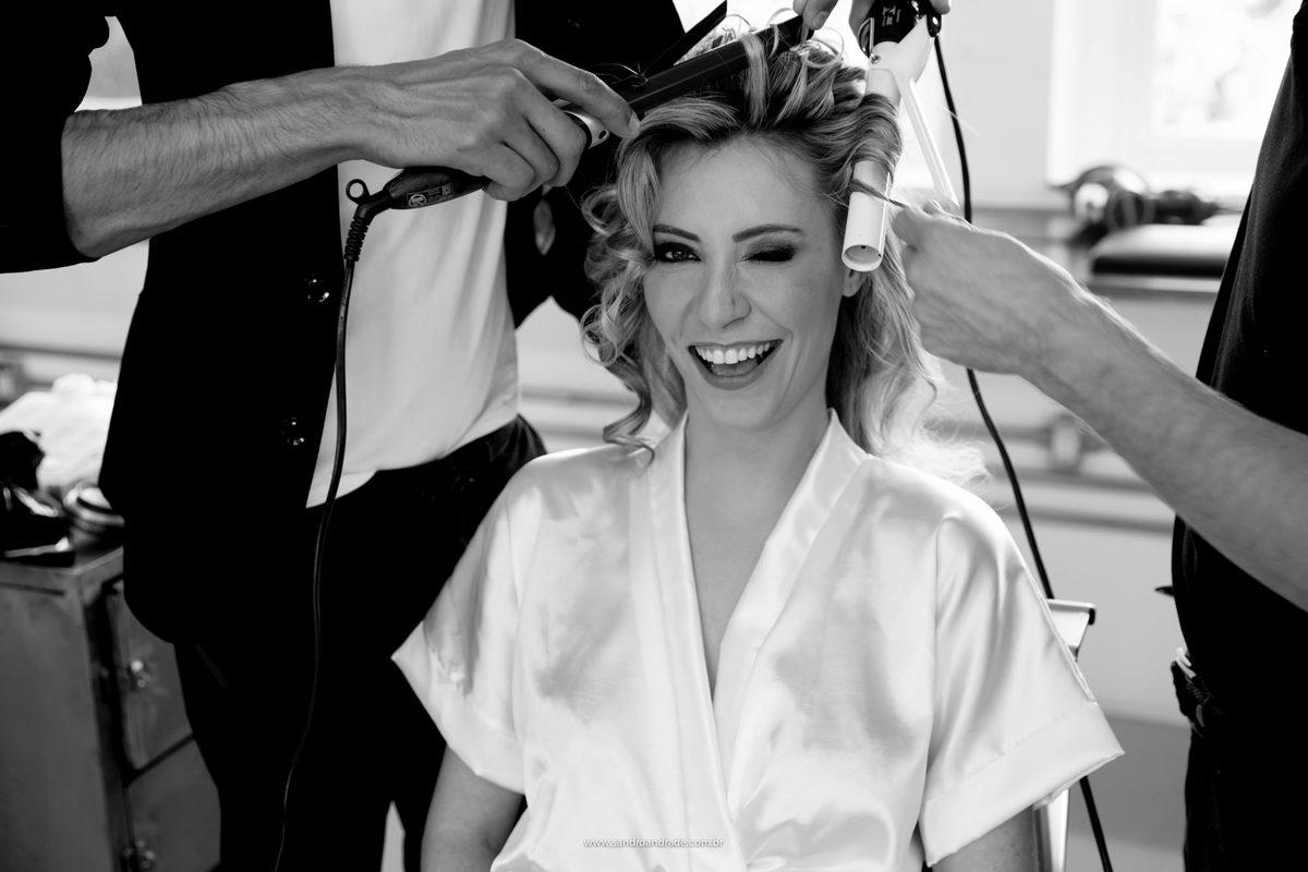 Preparação da noiva, montando o penteado e ela da uma piscadinha.
