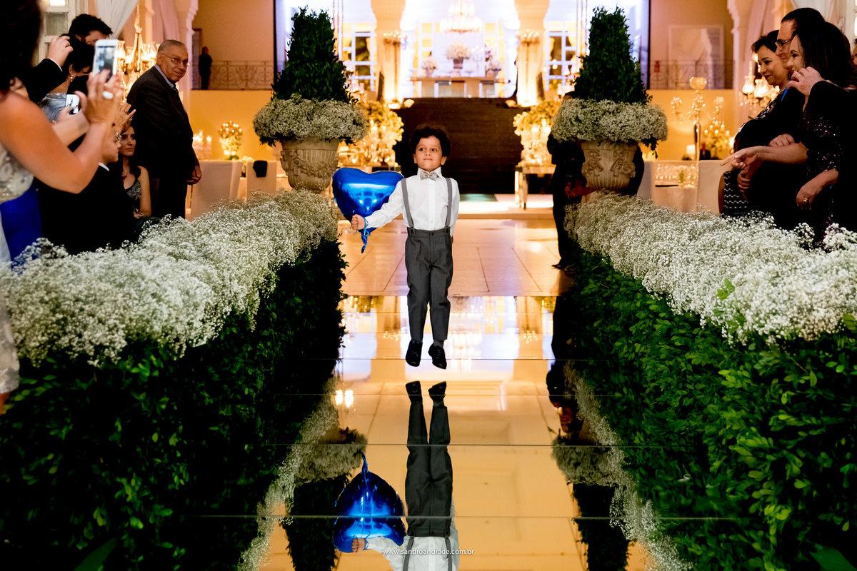 Entrada do pajen, parece estar flutuando fora do chão, uma fotografia inusitada ele entrou com um balão de coração azul.