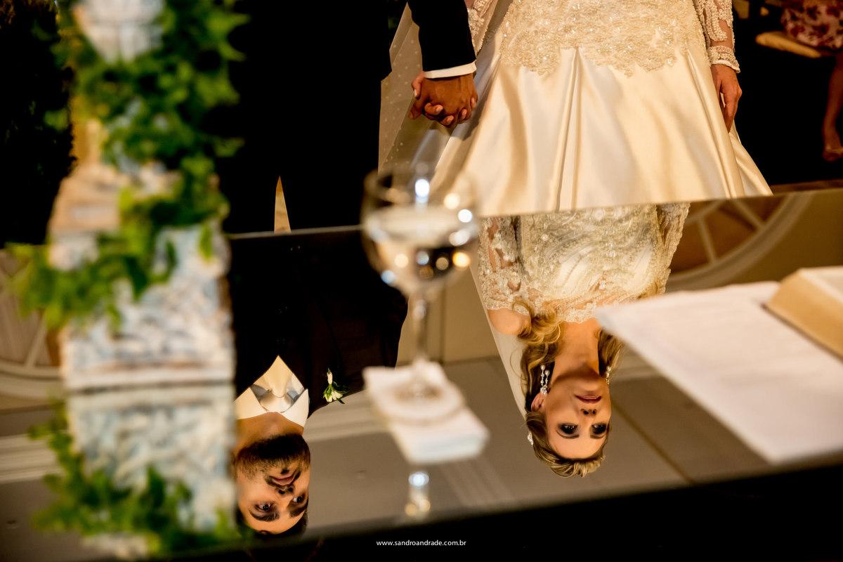 Lindo detalhe da cerimonia, os noivos de mãos dadas e abaixo o reflexo no espelho da mesa do pastor, o rosto dos noivos serenos.