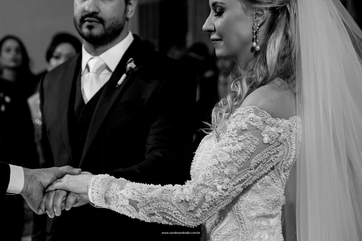 Detalhes, o rosto da noiva e aos dadas durante a benção das alianças de mãos dadas com o pastor.