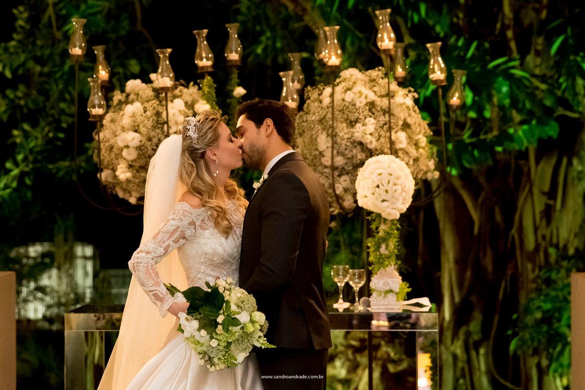 O beijo dos noivos, o beijo mais lindo com  a decoração de fundo, perfeita fotografia de casamento feita por Sandro Andrade.