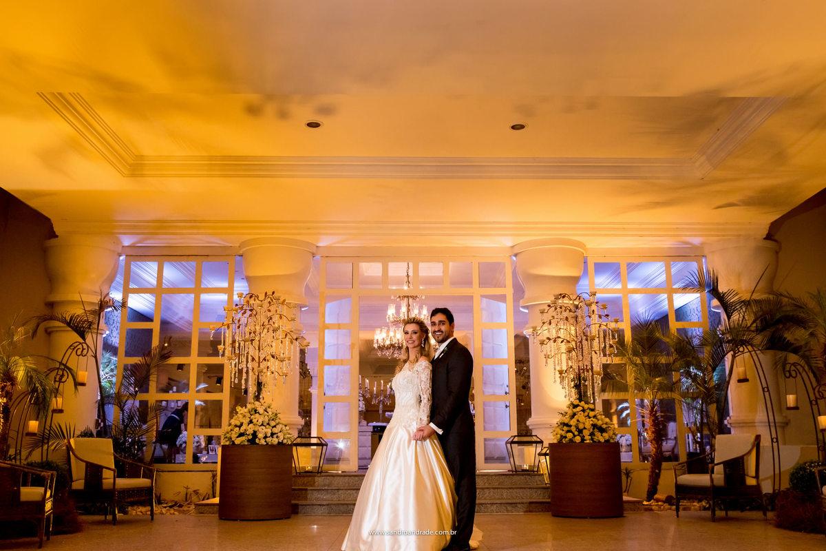 Na entrada do do salão de festas, eles fazem fotos para compor o album de casamento.