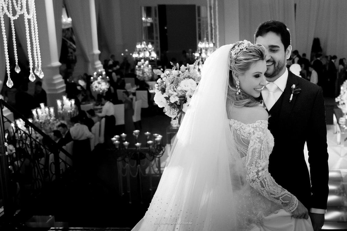 Fotografia linda em preto e branco, os noivos bem juntinhos, ele olhando para sua amada com ternura.