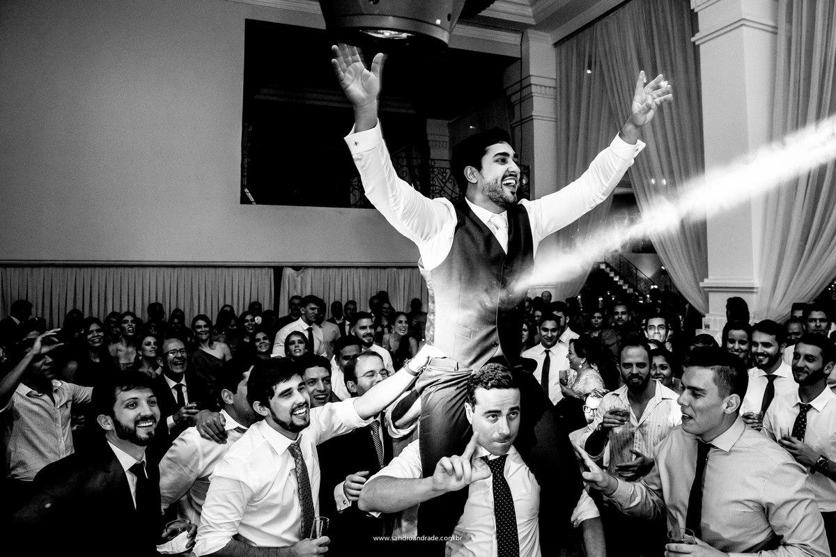 O noivo muito feliz sendo carregado pelos amigos na pista de dança.