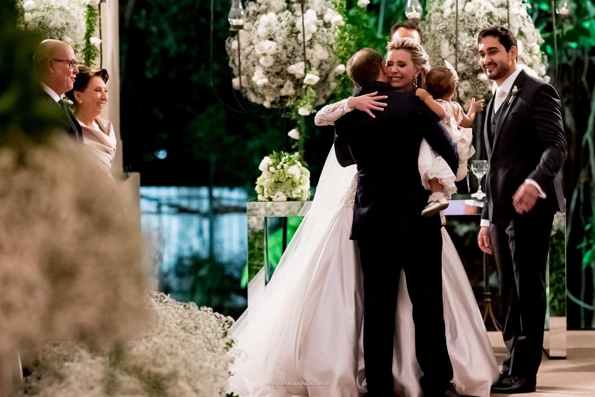 Emocionada, a noiva abraça seu irmão e a bebezinha, sua sobrinha que conduziram as alianças ao altar.