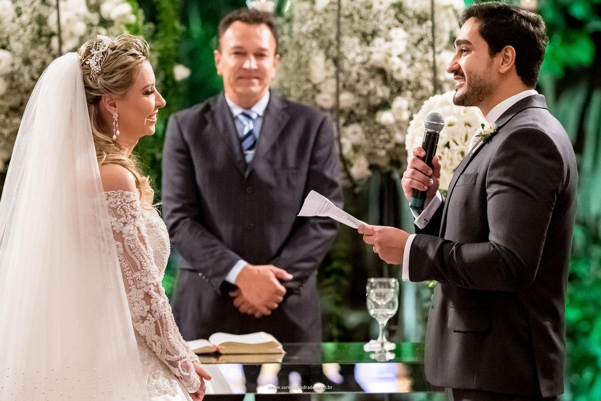 O noivo declarando os votos de amor e relembrando como a conheceu no carnaval de Salvador, eles sorriem felizes.
