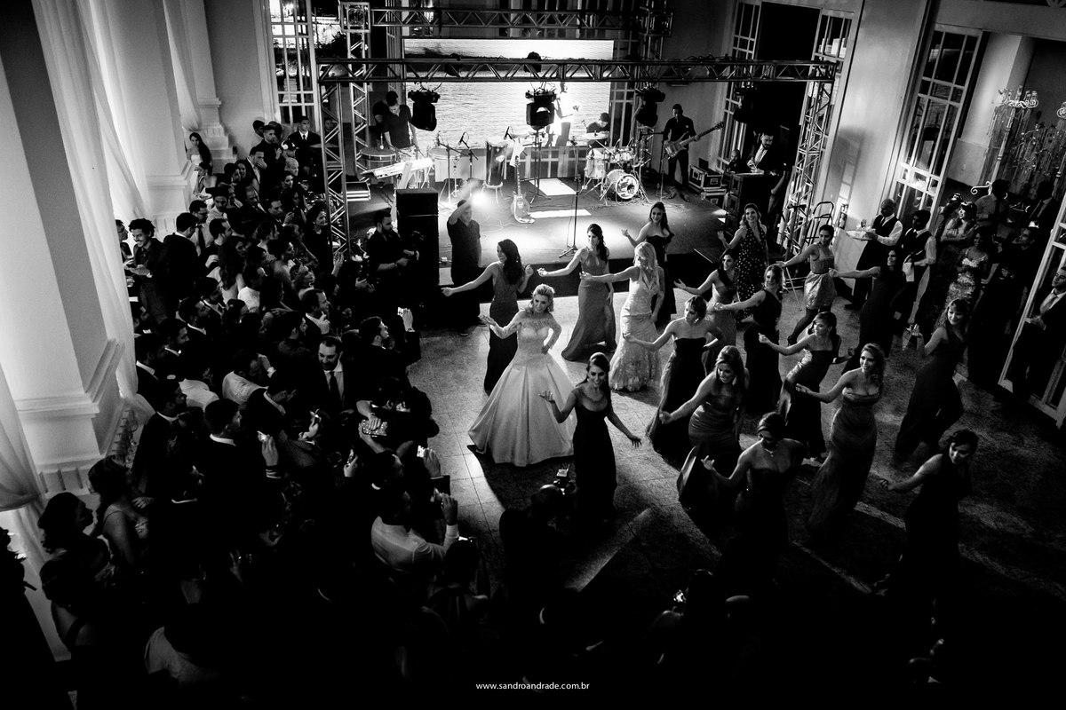 A noiva dançando em uma coreografia muito bem treinada com as amigas e todos ao redor da pista de dança observam.