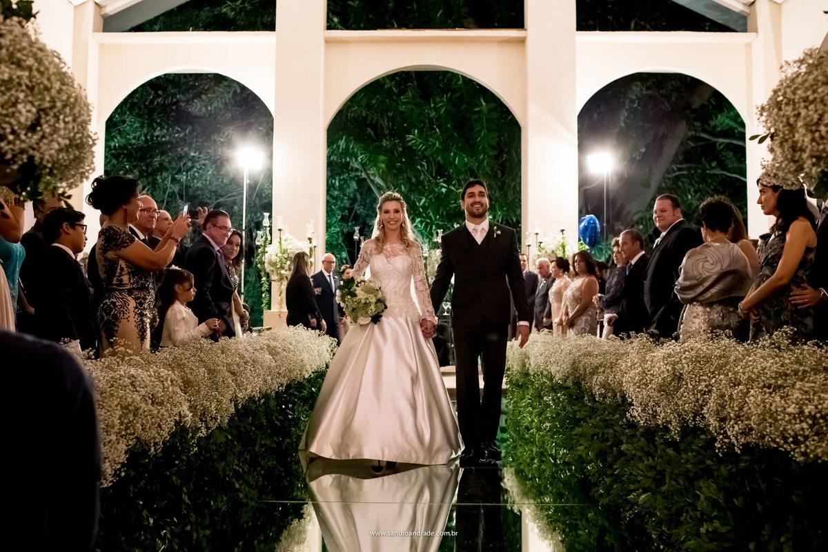 Saida dos noivos, felizes eles saem sorrindo para os convidados.