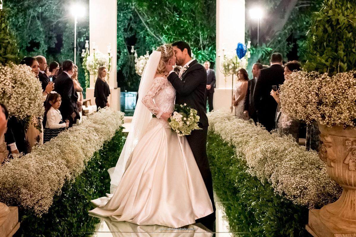 Beijo do mais novo casal de marido e mulher durante a saida da cerimonia, fotografia classica de casamento feita pelo fotografo premiado Sandro Andrade.