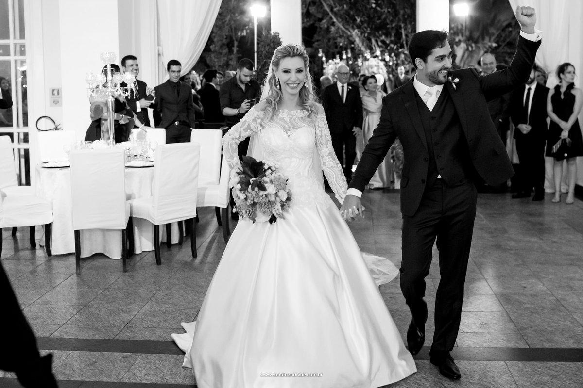 Saindo da cerimonia o noivo comemora com a mão para cima na entrada da festa.