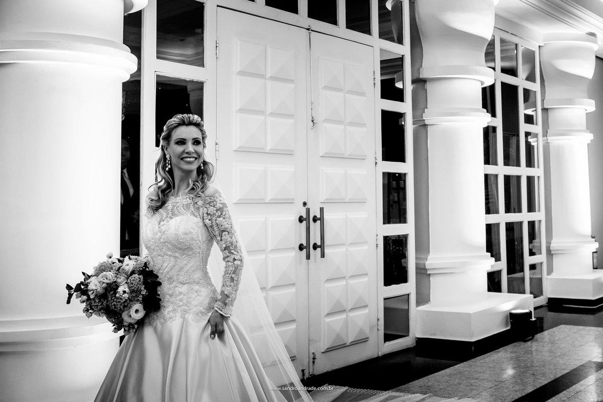 Linda fotografia preto e branco de detalhes do vestido de noiva e do lindo buque.