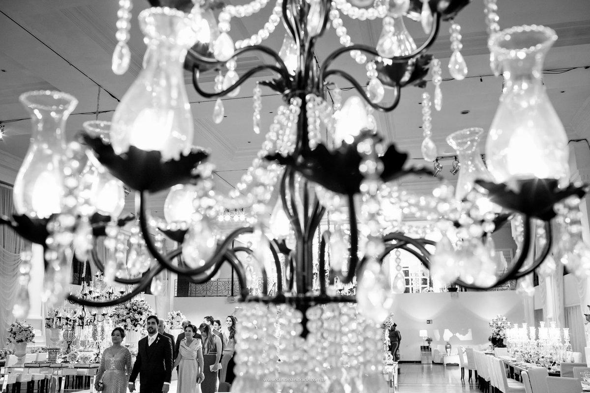 No detalhe do lustre, uma fotografia criativa em preto e branco, ao fundo a entrada do noivo, pais e padrinhos.