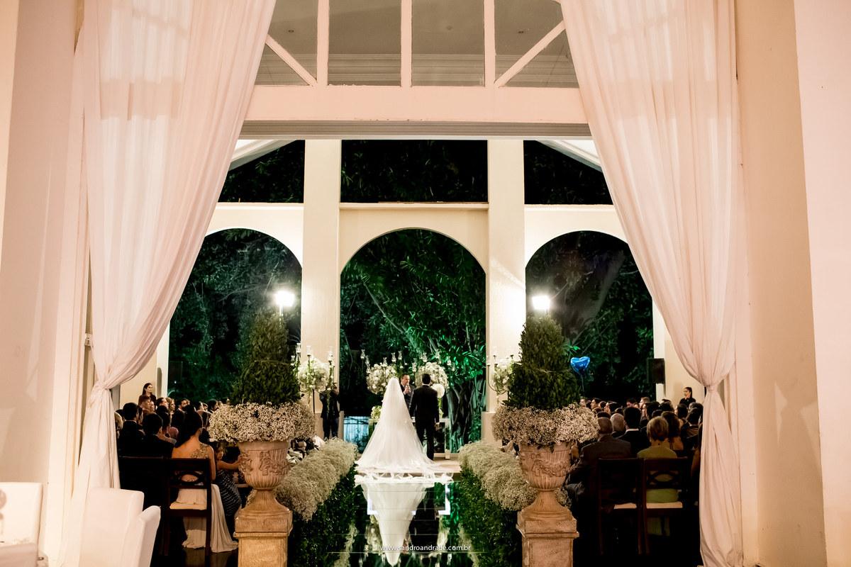 Imagem feita de tras, os noivos de costas no altar e os convidados, no espaço da corte, decoração linda.