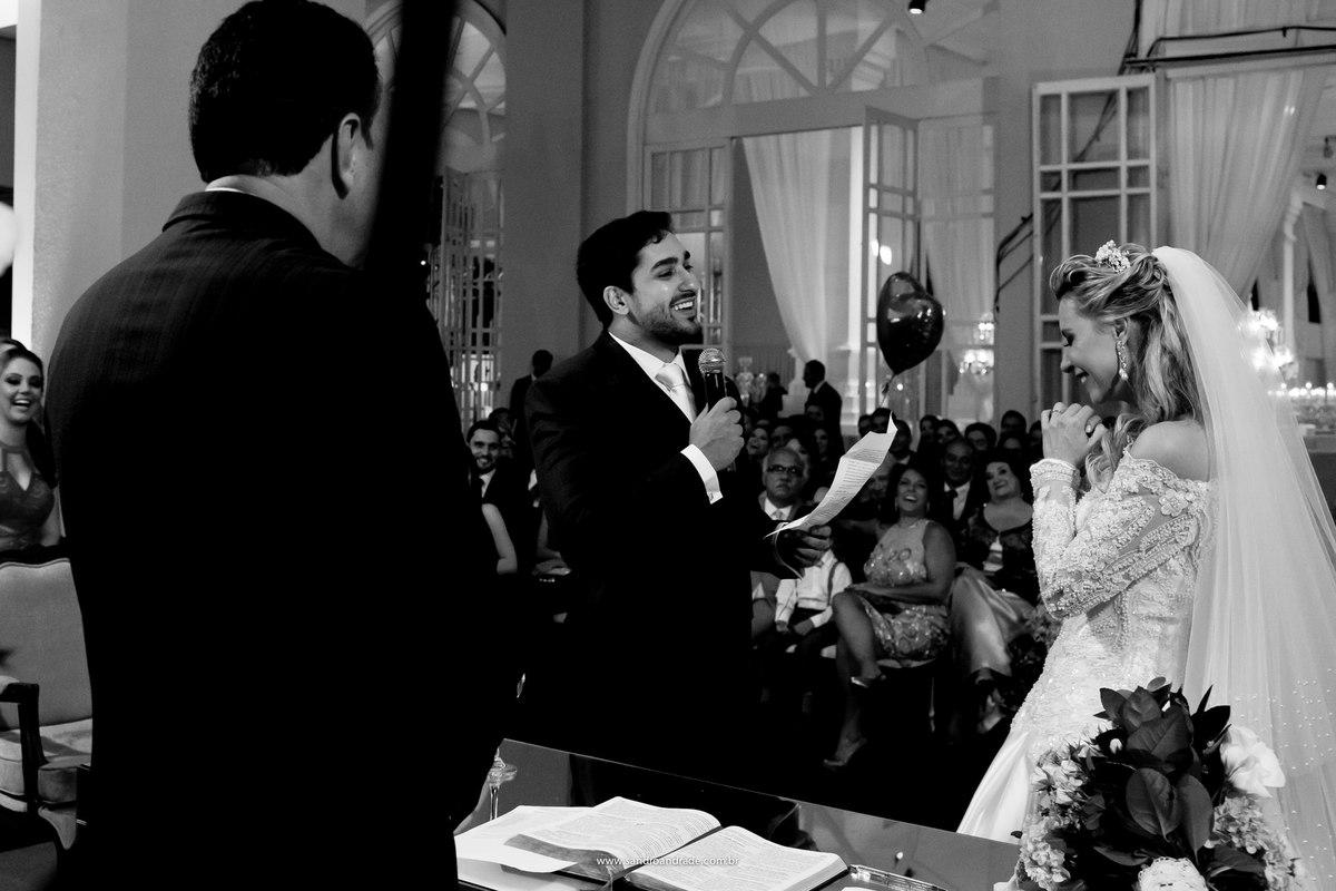 Os votos do noivo emociona os convidados que dão muitos sorrisos durante as palavras ditas a sua amada noiva, que emocionada se surpreende.