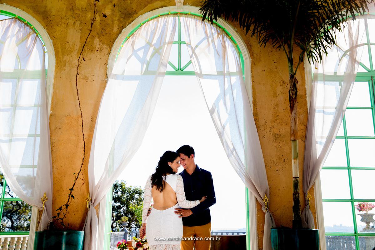 O casal paixonado, ela de costas e ele de frente a abraça, linda fotografia colorida.