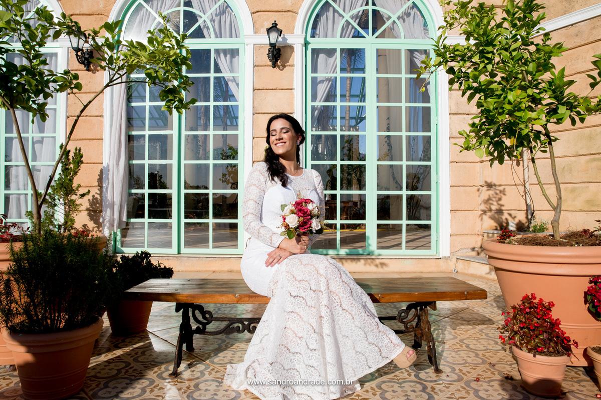 Com o sol forte no rosto ela senta no banco e de olhos fechados posa para Sandro Andrade um dos melhores fotografos de casamento de bsb.