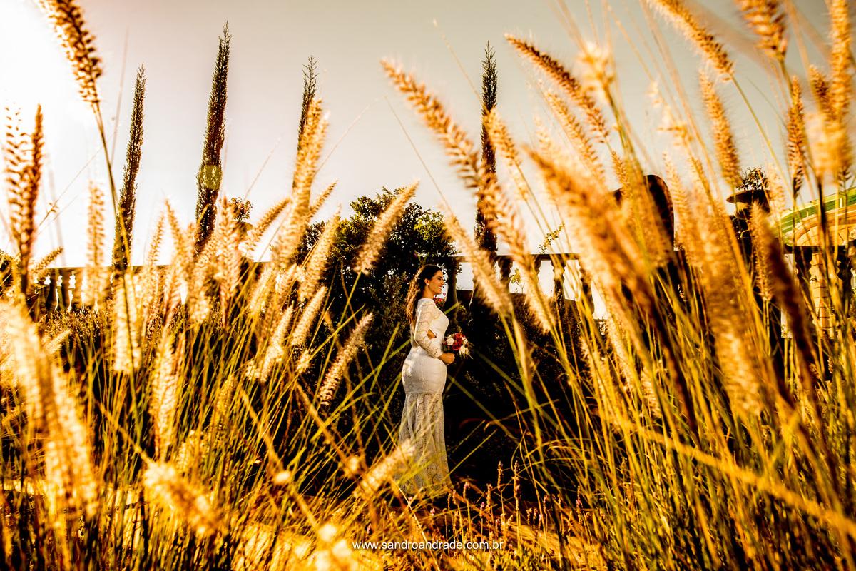 A noiva toda linda, fotografia colorida, luz do sol, vestida de branco e com seu lindo buque juntamente com esses trigos dourados.