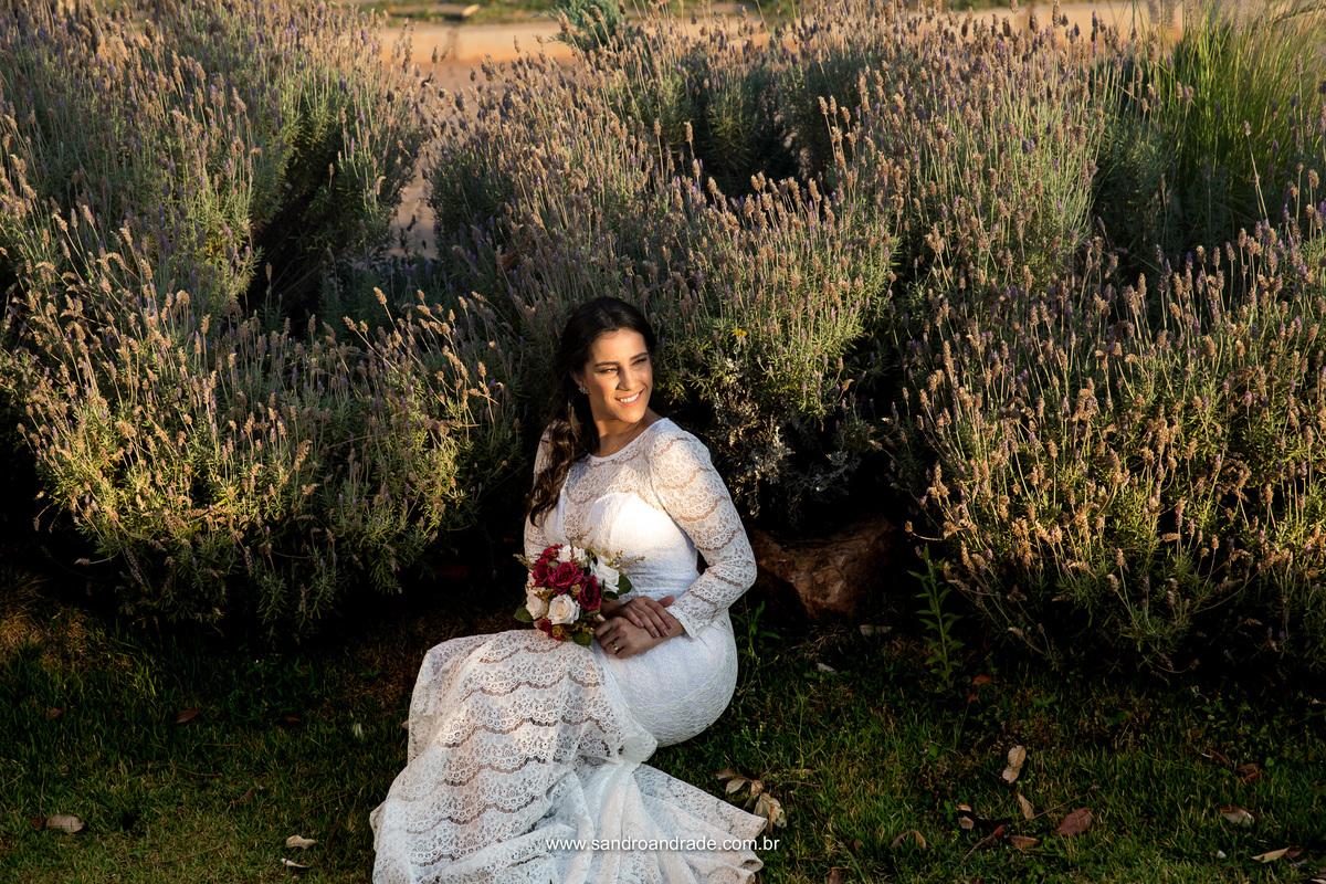 Sentada no meio das lavandas a noiva fotografa com seu lindo buque.