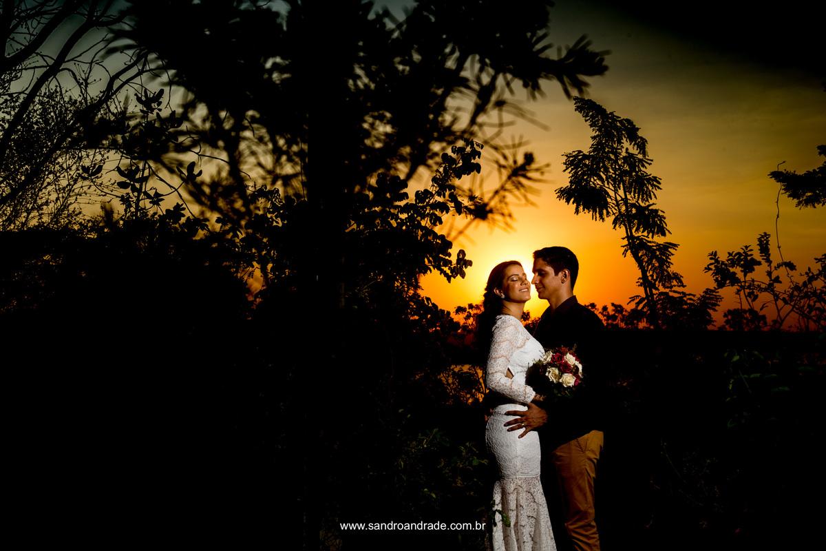O por do sol e sua belissima cor no céu, com arvores em silhueta e um casal apaixonado com uma luz criativa de Sandro Andrade fotografo de casamento no df.