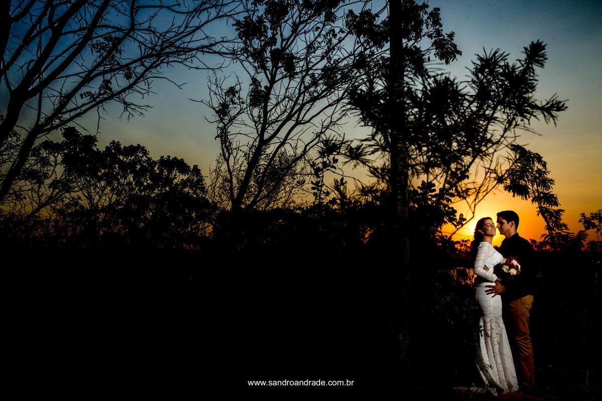 Linda fotografia de Sandro Andrade fotografo em brasilia, o casal ao fundo com o por do sol maravilhoso no céu brasiliense.