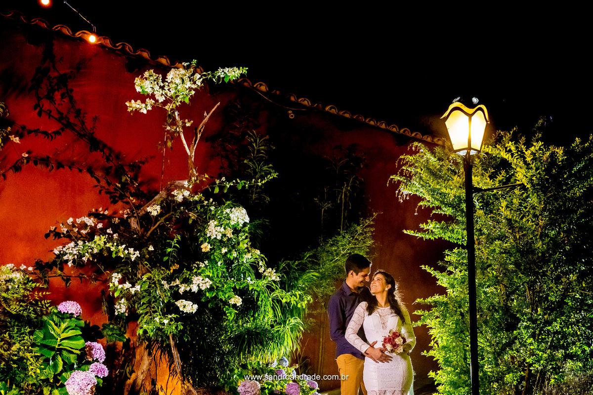 O casal se olhando em composiçao na lateral da casa com a luz e lindas hortensias.