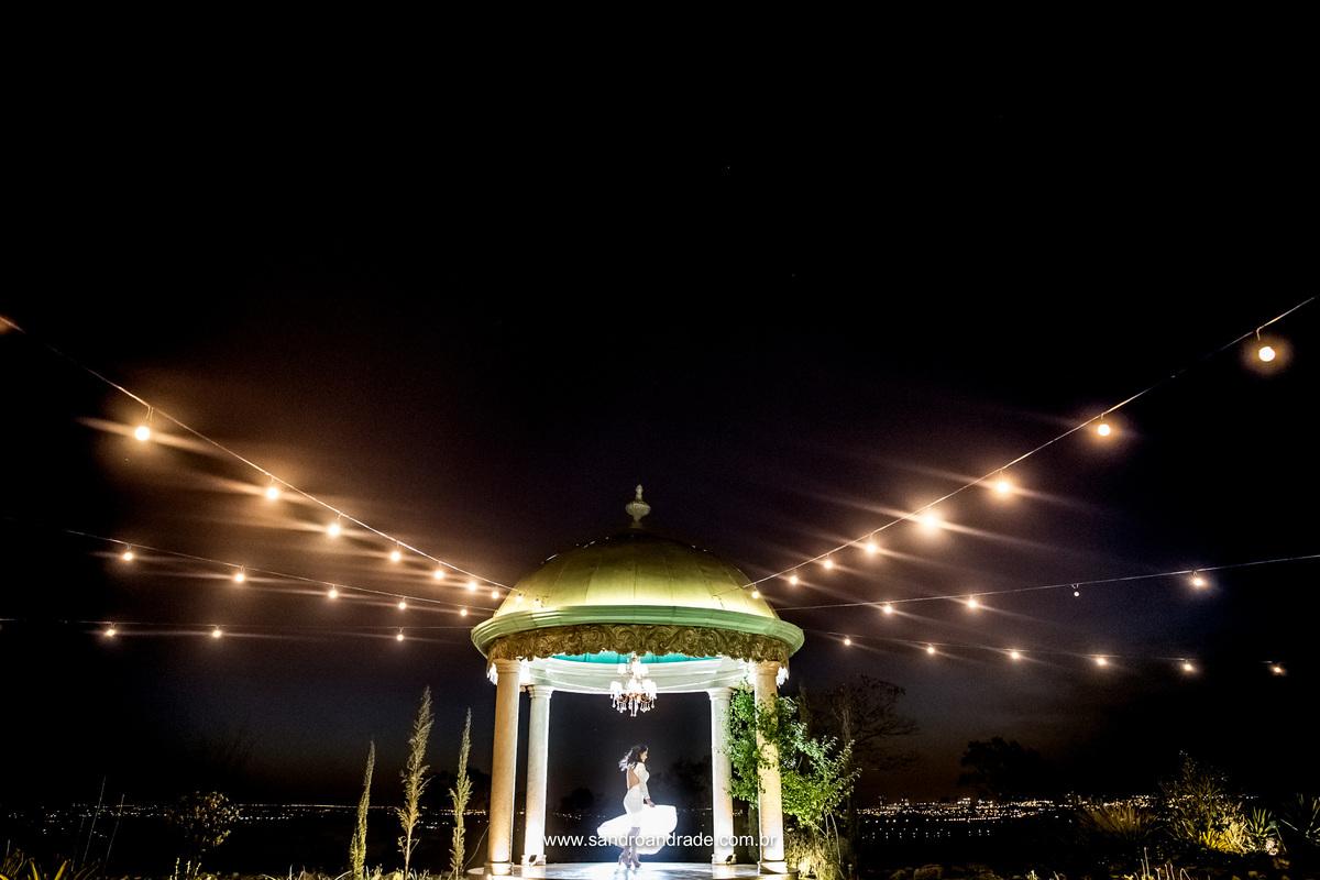 A noiva girando dentro do gazebo, fotografia de movimento, com um efeito fantastico do varal de luz.