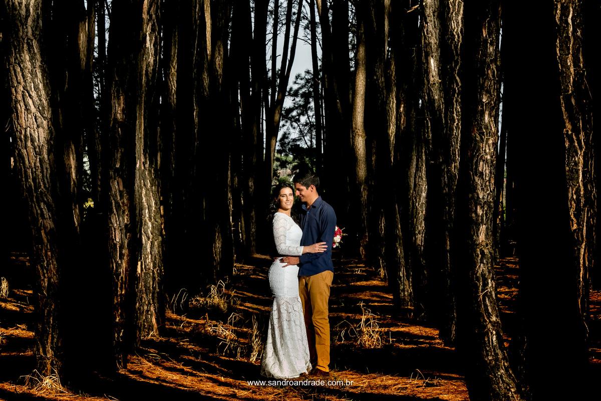 No meio dos eucaliptos o casal bem coladinhos e sorridentes, fotografia de corpo inteiro.