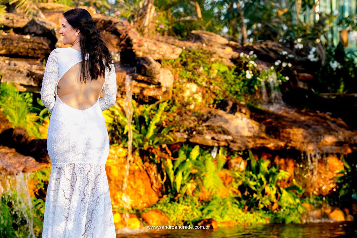 Na frente da cascata Jessica sorri e de costa mostra os detalhes de seu vestido de noiva.