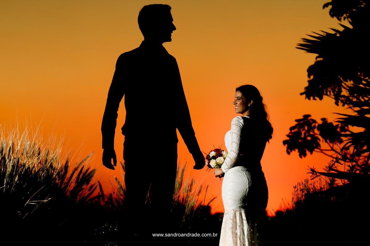 Fotografia linda e criativa de Sandro Andrade com a noiva iluminada e o noivo em silhueta.