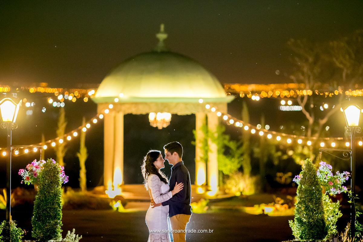 Simples e bonita, o casal se olhando entre as arvores e o gazebo de fundo com uma linda luz.