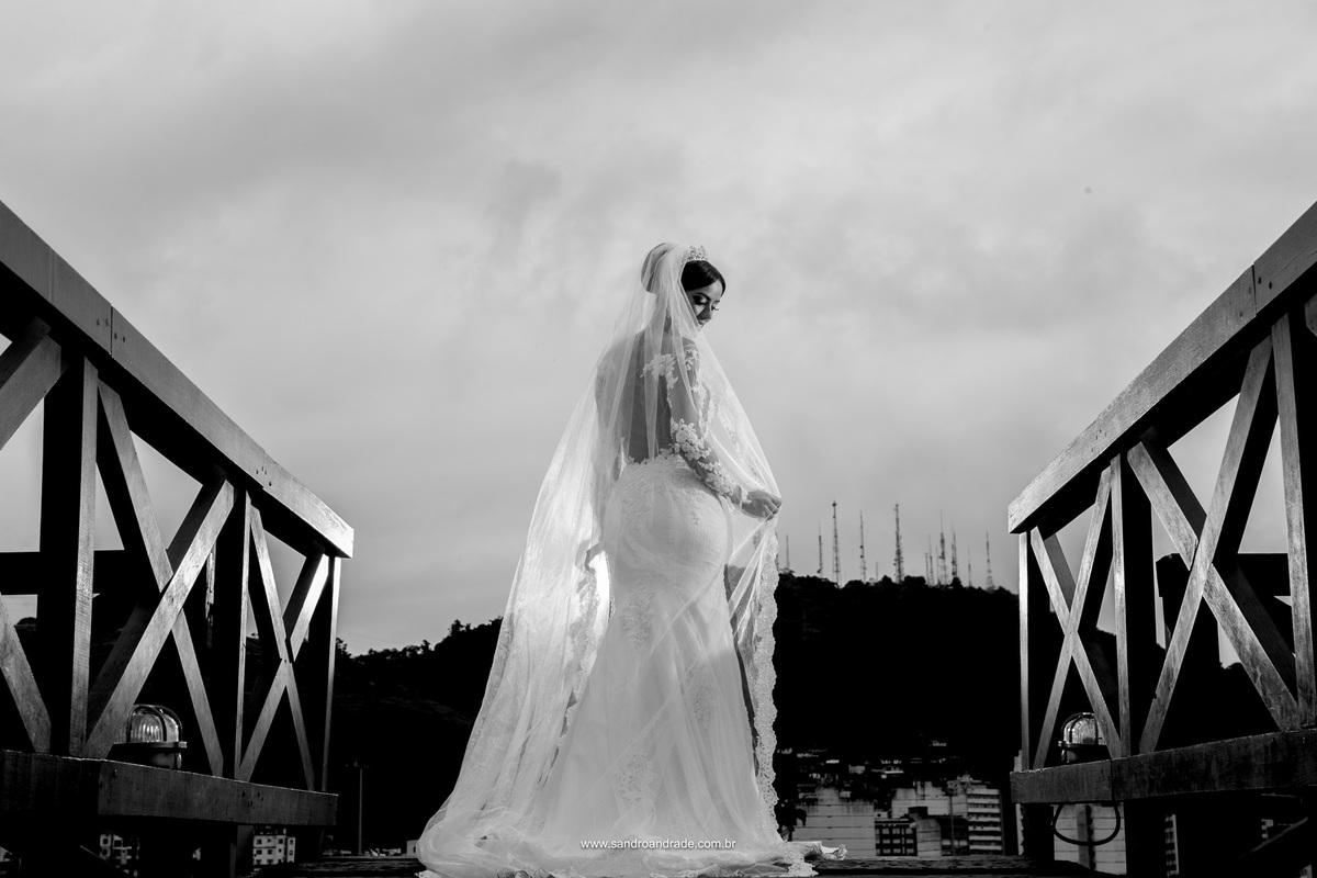 Uma noiva linda, fotografie me preto e branco pegando o vestido e a mantilha da noiva na ponte do museu da Valle em Vila Velha.