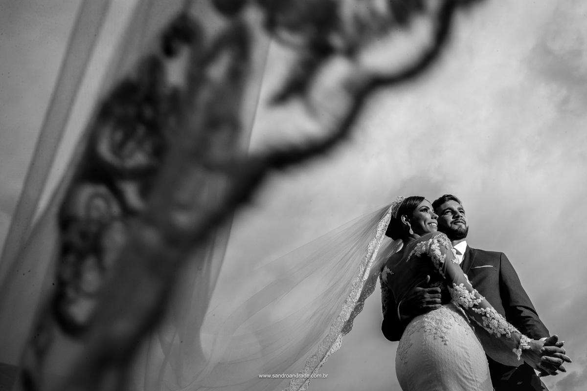 Em detalhes do véu compus esta fotografia com o casal, abraçadinhos, sorrindo e felizes.
