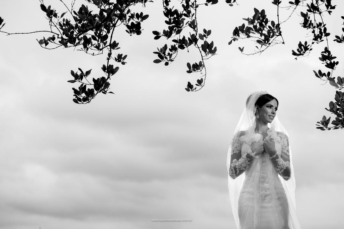 Preto e branco, uma fotografia da noiva segurando seu véu.
