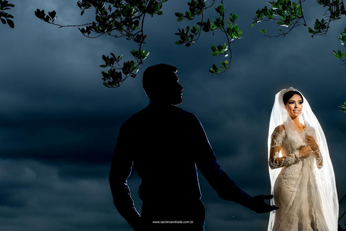 Luz criativa e silhueta, Sandro Andrade fotografo de casamento combinou perfeitamente nesta fotografia da noiva em destaque colorido e o noivo em silhueta estendo a mão para sua amada esposa.